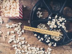 Film reel with popcorn and tickets Stock Photos