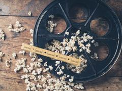 Film reel with popcorn and tickets - stock photo