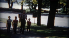 1955: Proud dad walking with 3 sons in tow on a sunny summer day. Stock Footage