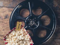 Film reel and popcorn Stock Photos