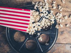 Film reel and popcorn - stock photo