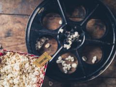 Film reel and popcorn Stock Photos