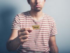 Sad man with cinema ticket - stock photo