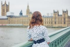 Woman on bridge at houses of parliament - stock photo