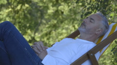 Mature man relaxing on a deck chair in his garden. Stock Footage