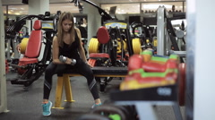 attractive, cute girl with blond hair is engaged in the gym, lifting weights and - stock footage