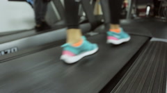 Stock Video Footage of gym, training on a treadmill, a girl in her favorite sneakers front of the