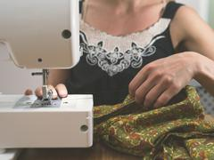 Young woman sewing with machine - stock photo