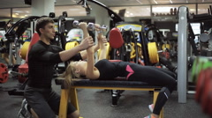 Stock Video Footage of male athlete the coach helps young attractive woman in the gym to engage in the