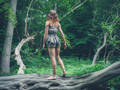 Barefoot woman standing on a fallen tree in the forest - stock photo