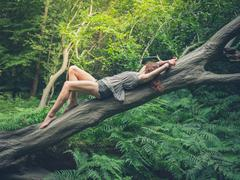 Sensual young woman on fallen tree in forest Stock Photos
