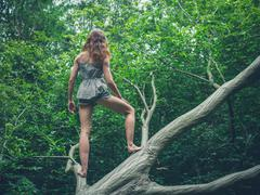 Barefoot young woman standing on fallen tree - stock photo
