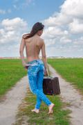 Attractive topless woman with suitcase Stock Photos
