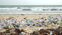 Pan across polluted beach  with plastic bottles Stock Footage
