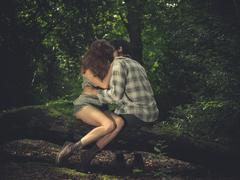 Young couple sitting on log and kissing - stock photo