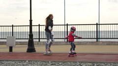 Mom and daughter learn to roller skate - stock footage