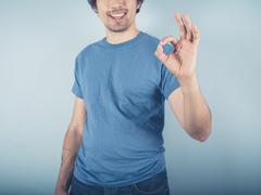 Happy young man showing ok sign Stock Photos