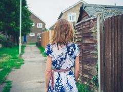 Young woman walking residential neighbourhood Stock Photos