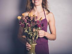 Young woman with dead flowers - stock photo