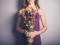 Young woman with dead flowers Stock Photos