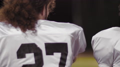 View from behind of players watching their team from the sidelines - stock footage