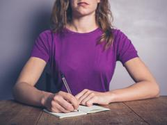Thoughtful young woman writing in notepad Stock Photos