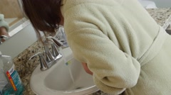 Dolly shot of woman brushing her teeth in robe Stock Footage