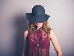 Happy young woman in hat and see through shirt - stock photo
