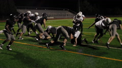 A football player gets tackled and trips over another player during a game Stock Footage