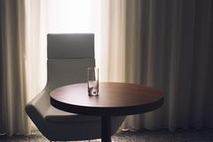 Empty glass on hotel room table - stock photo
