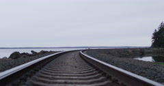 Slow motion push with DJI Ronin across railroad tracks on Northwest bay Stock Footage
