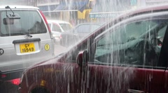 Shower heavy rain water flow on parked cars on city street Stock Footage