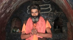 Indian sadhu holy man prays in holy cave along  Ganges River. Devprayag, India Stock Footage