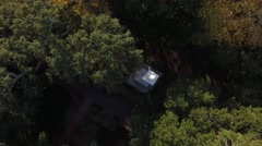 Aerial Shot Descending Between the Trees Focused on an Alabaster Statue in a Tow Stock Footage