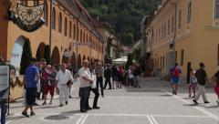 Tourists walking on a main alley (Apollonia Hirscher) in the center of Brasov Stock Footage
