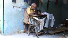 Indian street tailor working on a foot sewing machine. Devprayag, India Stock Footage