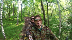 Two guys on quad ride through the forest Stock Footage