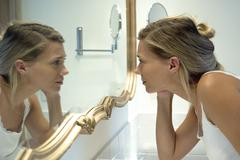 Stock Photo of Woman looking at self in bathroom mirror