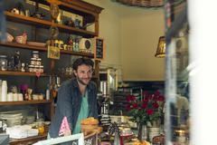 Shopkeeper behind counter at coffee shop Kuvituskuvat