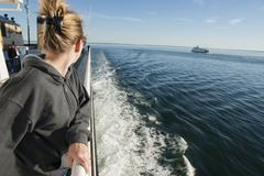 Woman standing on deck of ferry boat, looking over shoulder at view - stock photo