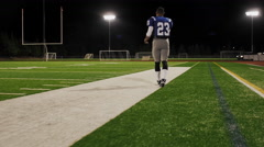 Football player as he walks down the field and throws the ball Stock Footage