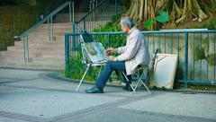 Street artist in front of his easel, painting with watercolors in Hong Kong - stock footage