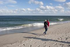 Stock Photo of Vacationer walking on beach with small child on back during the off season