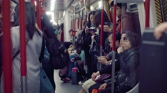 Many commuters, crowded onto a subway car in Hong Kong, at night Stock Footage