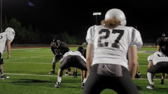 A football player tackles his opponent and another player dives on the ball - stock footage