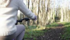 Little girl rides her bicycle in the woods, in slow motion Stock Footage
