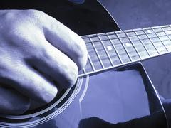 Closeup photo of an acoustic guitar played by a man - stock photo