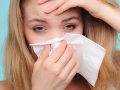 Flu allergy. Sick girl sneezing in tissue. Health Stock Photos