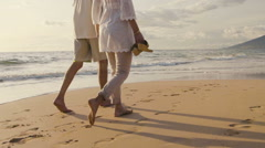 Slow Motion Older Couple Holds Hands and Walks Down the Beach at Sunset Getti - stock footage