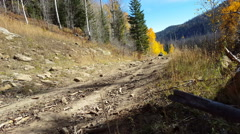 Side by side UTV approaching camera rocky dirt road autumn colors Arkistovideo